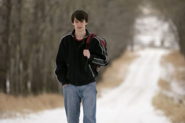 Young man walking up a snowy road