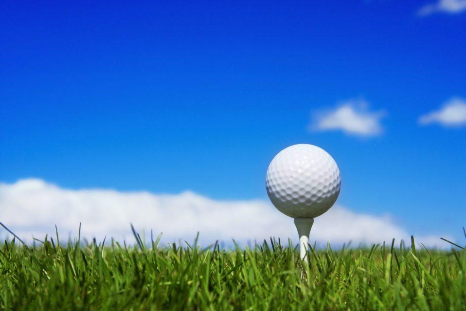 Golf ball teed up against blue sky